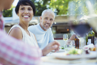 Couple smiling at table outdoors - CAIF04898
