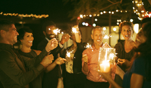 Friends playing with sparklers at party - CAIF04919