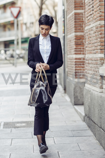 Portrait of young businesswoman  with bag walking on pavement - JSMF00058