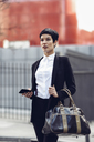 Portrait of fashionable young businesswoman with cell phone and bag - JSMF00061