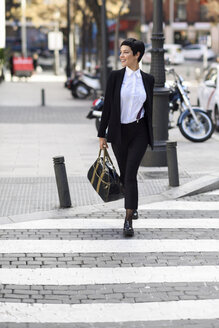 Smiling young businesswoman crossing street - JSMF00064