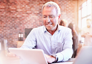 Smiling businessman using digital tablet in office - CAIF04924