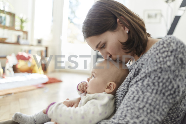 Mother kissing baby daughter on the head - CAIF04936