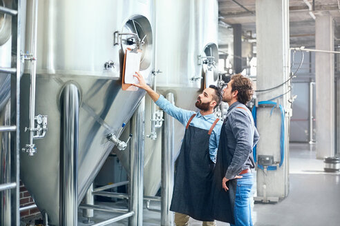 Male brewers checking clipboard on vat - CAIF04954