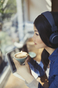 Pensive young woman drinking coffee, listening to music with headphones at cafe window - CAIF04984