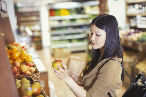 Young woman shopping, examining apple in grocery store - CAIF04987