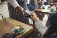 Customer with credit card paying worker with contactless payment in cafe - CAIF04996