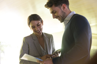 Smiling businessman and businesswoman discussing paperwork - CAIF05029