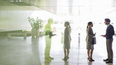 Business people talking in office lobby - CAIF05035