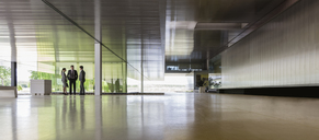Business people talking in distance in modern office lobby - CAIF05068