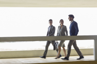 Business people walking and talking along walkway - CAIF05074