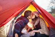 Young couple camping, kissing inside tent - CAIF05092
