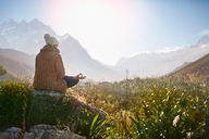 Young woman meditating on rock in sunny, remote valley - CAIF05101
