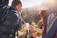 Young couple hiking, taking a coffee break and using smart phone - CAIF05134