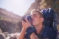 Young man with backpack hiking and photographing with camera - CAIF05137