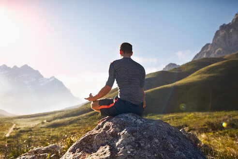 Young man meditating on rock in sunny, remote valley - CAIF05143