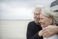 Affectionate senior couple hugging and looking away on beach - CAIF05167