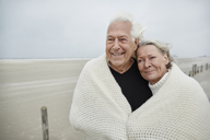 Smiling affectionate senior couple wrapped in a blanket on beach - CAIF05170
