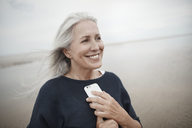 Smiling senior woman holding cell phone on winter beach - CAIF05173