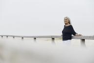 Confident senior woman leaning on beach boardwalk railing - CAIF05176