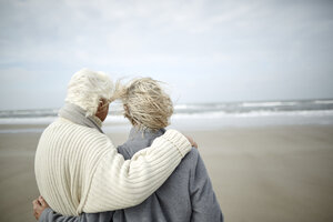 Pensive senior couple hugging and looking at ocean view on windy winter beach - CAIF05179