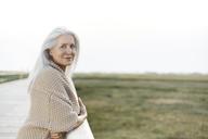 Portrait confident senior woman leaning on boardwalk railing - CAIF05182