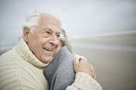 Affectionate senior couple hugging on winter beach - CAIF05185