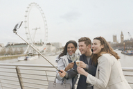 Smiling friend tourists celebrating, toasting champagne and taking selfie with selfie stick near Millennium Wheel, London, UK - CAIF05200