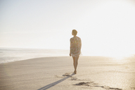 Pensive, serene woman walking on sunny summer beach - CAIF05248