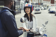 Smiling young woman on motor scooter talking to friend on sunny urban street - CAIF05275