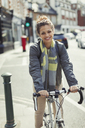 Portrait smiling young woman commuting, riding bicycle on sunny urban street - CAIF05278
