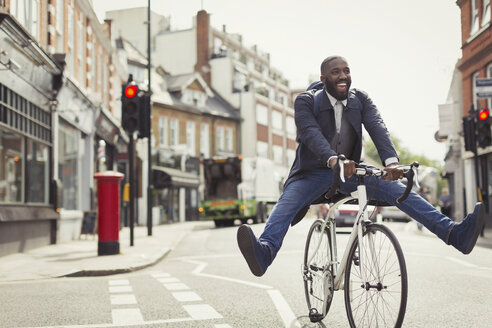 Playful young businessman commuting, riding bicycle on urban street - CAIF05284