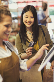 Female cashier helping smiling customer with credit card at grocery store cash register - CAIF05287