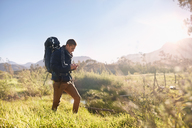 Young man with backpack hiking, checking compass in sunny, remote field - CAIF05305