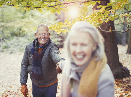 Playful senior couple holding hands in autumn park - CAIF05314