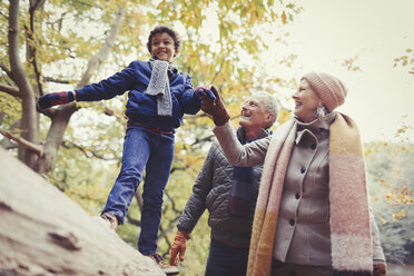 Grandparents walking grandson on log in autumn park - CAIF05317