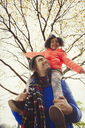 Father carrying enthusiastic daughter on shoulders below autumn tree in park - CAIF05320