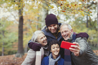 Multi-generation family taking selfie with camera phone in autumn woods - CAIF05329