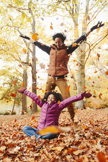 Playful mother and daughter throwing autumn leaves in park - CAIF05335