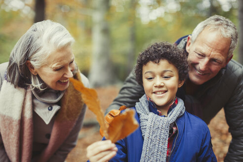 Grandparents and grandson holding autumn leaf - CAIF05341