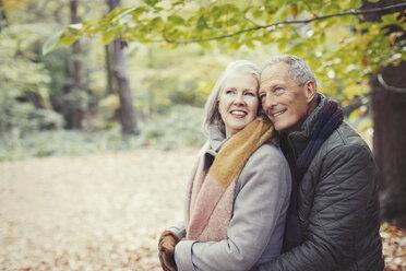 Smiling senior couple hugging in autumn park - CAIF05347