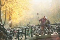 Young couple with bicycles taking selfie with selfie stick on autumn bridge, Amsterdam - CAIF05353