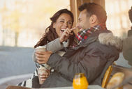Playful young couple with milkshake at sidewalk cafe - CAIF05365