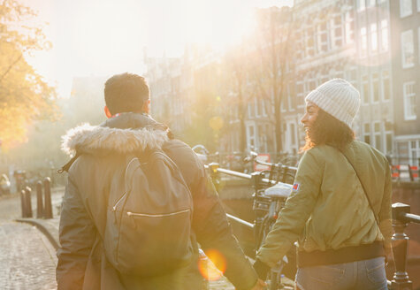 Young couple holding hands walking on sunny urban autumn street, Amsterdam - CAIF05374