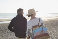 Mature couple looking way on sunset beach - CAIF05386