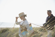 Mature couple with fishing rod walking in sunny summer beach grass - CAIF05389