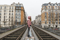 France, Paris, woman standing between abandoned railway tracks - AFVF00281