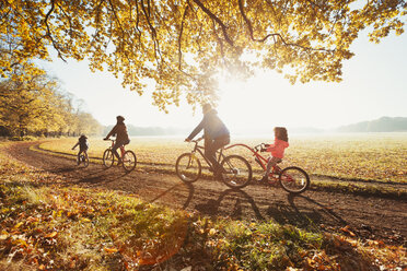 Young family bike riding in sunny autumn park - CAIF05431