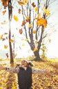 Playful girl throwing leaves overhead in sunny autumn park - CAIF05434