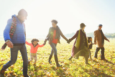 Family holding hands walking in sunny autumn park - CAIF05437